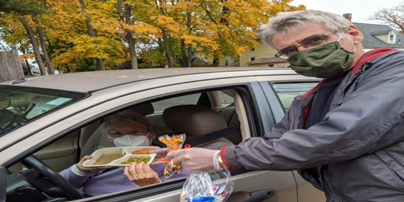 Volunteer serves lunch at Grab and Go event October 2020